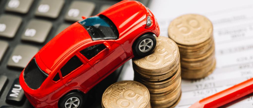 Carro color rojo sobre una mesa con monedas.