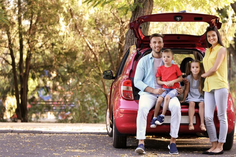 Familia feliz con coche nuevo